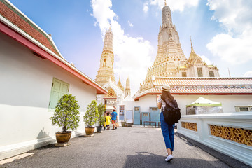 Tourist women with Carrying a backpack Viewing poster, About the temple in Bangkok At Arunratchawararam Temple.