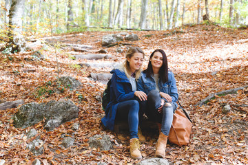 Two young girls girlfriend sat down to rest in autumn forest. Walk in the woods. Girlfriends hiking in the fall.