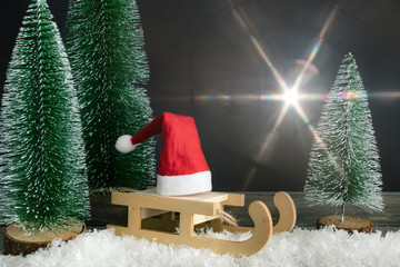 Christmas decoration with a red Santa Claus hat on a sledge beside fir trees and light flare