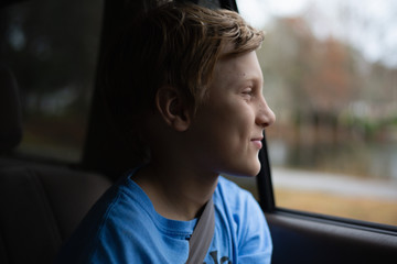 Portrait of a boy riding in a car with the window open.