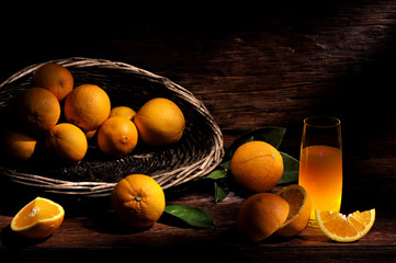 basket of orange fruits with an orange juice glass.  on a wooden wood table, in light painting