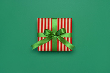 Gift box with green ribbon on green background top view flat lay. Holiday concept, birthday gift, new year or Christmas gift box presents Xmas holiday. Congratulations background with space for text.