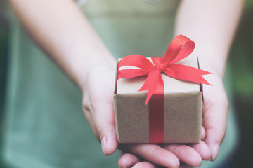Female hands holding a small gift wrapped with red ribbon. Selective focus,Selective focus,Valentines day
