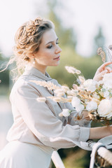 Beautiful bride in front of wedding arch with flowers and decor. Bouquet in the hands and details. The girl is happy, smiling and dancing. Dream wedding dress in modern style