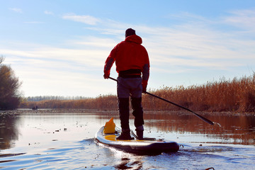 Man rowing with a paddle on the stand up paddle board (paddleboard, SUP) in the Danube river at calm cold winter day