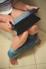 Woman using tablet pc in the toilet.