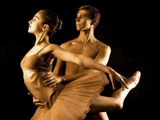 Professional, emotional ballet dancers on dark scene performed by sexual couple with golden body art.Shining gold skin.Pair depicts love and passion on stage