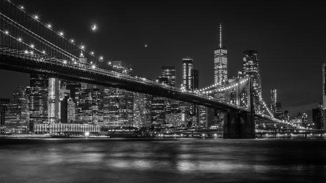 Brooklyn Bridge in New York mit Manhattan Skyline bei Nacht in schwarz/weiß