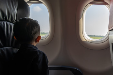 Little boy looking out of window in airplane, lonely and homesick concept, low key