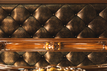 Close-up Gold fabric upholstered headboard with buttons textile background, retro Stylish bedroom furniture with reflection in the mirror