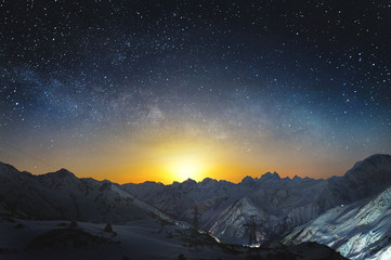 Canvas Prints Night blue Moonset in the mountains at night with a horizontal milky way on the sky. Snow covered peaks of mountains at night