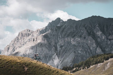 mountain biker riding downhill with dramatic mountain backdrop
