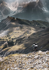 Maritime Alps - mountain biker descending from a summit with dramatic mountain backdrop in the Alps