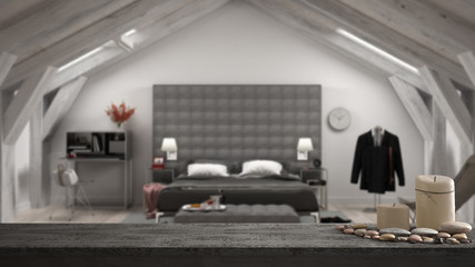 Wooden vintage table top or shelf with candles and pebbles, zen mood, over blurred contemporary gray bedroom in luxury attic, bed and carpet, classic architecture interior design