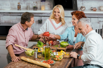 smiling old mature friends preparing salad for dinner and talking at home