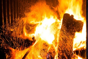 Firewood in the stove for heating. Sparks from the fire rise up. The temperature of the planet is very high.