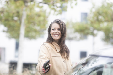 Junge Frau checkt Carsharing Auto