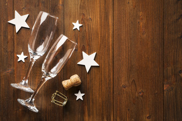 New year champagne glass and wihte stars on old wooden floor