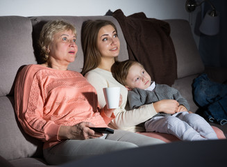 Woman with her mother and son are watching film in time evening rest