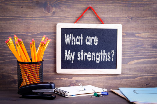 what are my strengths question. Business success concept. Chalkboard on a wooden background