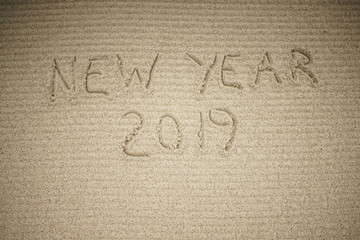 background with the inscription of the new year 2019 on the sand of yellow color