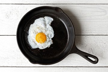Fond de hotte en verre imprimé Ouf Single fried egg in cast iron frying pan sprinkled with ground black pepper. Isolated on white painted wood from above.