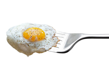 Single fried egg sprinkled with ground black pepper resting on metal spatula isolated on white.