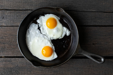 Two fried eggs in cast iron frying pan isolated on dark painted wood from above.