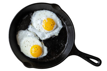 Foto auf Acrylglas Eier Two fried eggs in cast iron frying pan sprinkled with ground black pepper. Isolated on white from above.