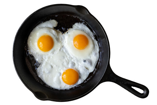 Three fried eggs in cast iron frying pan isolated on white from above.