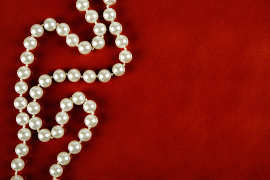 White pearl necklace on red leather background.
