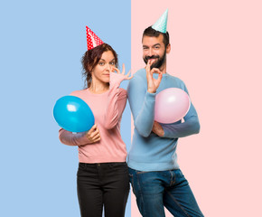 couple with balloons and birthday hats showing an ok sign with fingers on pink and blue background