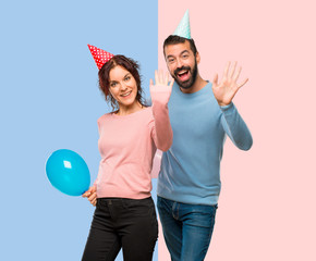 couple with balloons and birthday hats saluting with hand with happy expression on pink and blue background