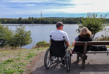 Man in a wheelchair next to a bench with his wife