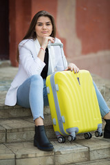 beautiful caucasian girl with long hair holding a big yellow suitcase. Concept - travel tourism