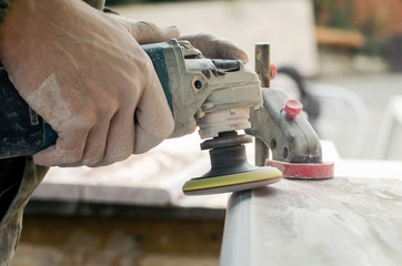 A man polishing a gray marble stone with a small angle grinder. working man the creation of monuments Wall mural