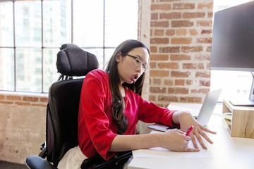 Woman with muscular dystrophy working in office