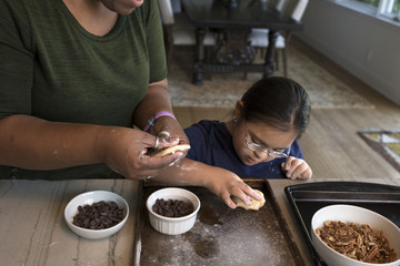 Woman teaching girl to make cookies