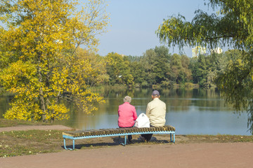 Older people are resting together sitting on a bench. Autumn morning at the couple in love.