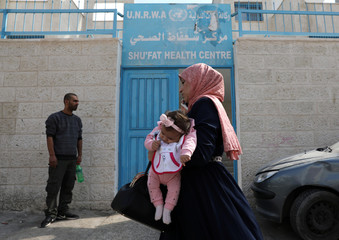 Palestinian woman holds a baby as she walks past the entrance to an UNRWA health center in the Shuafat refugee camp in East Jerusalem