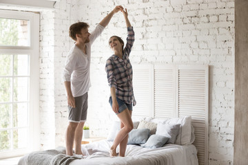 Young couple in love standing in bedroom having fun at home. Woman and man holding hands dancing enjoying date spending time together. Just a married romantic relations or relocate at new home concept