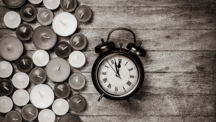 Retro alarm clock with candles on wooden background. Image in black and white color style