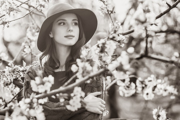 Portrait of a beautiful woman near blossom apple tree garden in spring time on sunset. Image in black and white color style