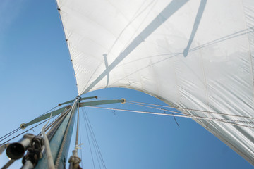 Foto op Plexiglas Zeilen White sail of a sailing boat against sky. Sails of river sailing yacht in the wind against the blue sky