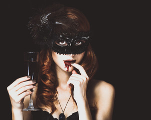 Redhead vampire woman in mask with glass of blood. Photo in vintage style.