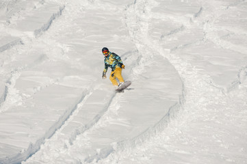 Snowboarder in bright sportswear riding down a snow hill on bright winter day