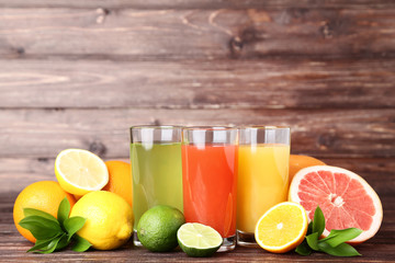 Citrus juice in glasses with fruits on brown wooden table
