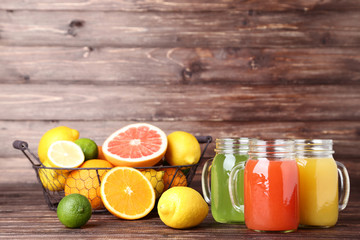 Citrus juice in glass jars with fruits on wooden table