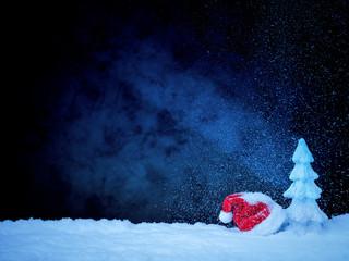 Weihnachtseisbaum vor tiefblauem Hinterdrund mit Schnee und Nikolausmütze