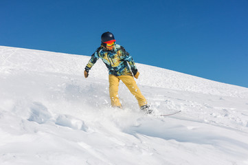 Professional man snowboarder in bright sportswear riding down a mountain slope